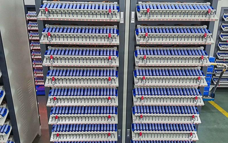 Batteries charging on charging racks.